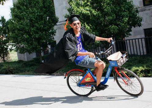 A graduate in cap and gown riding a KU bicycle