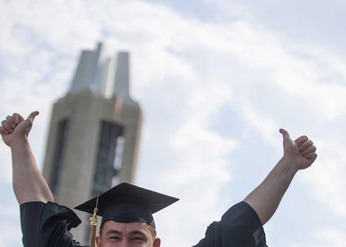 A graduation gives a thumbs up in front of the campenille