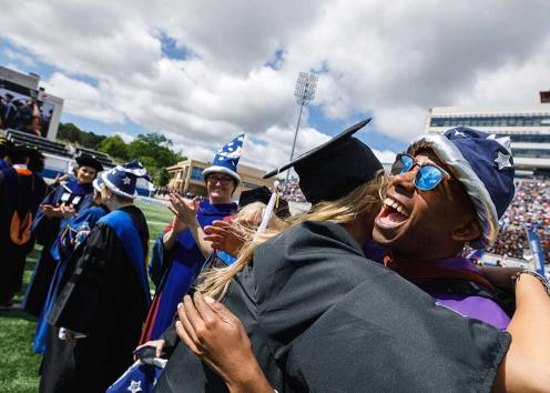 Graduates in wizard hats hugging